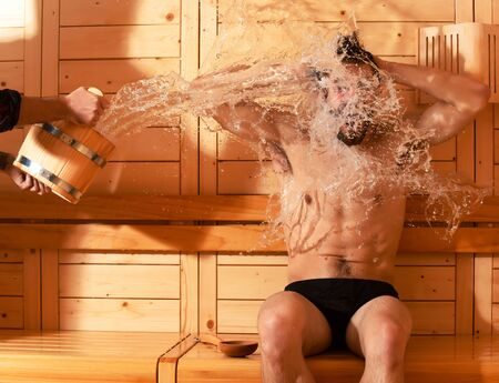 bather: Excited man or bather with muscular sexy torso, body, wet with big splash of water from bucket in sauna, thermal bath on wooden background