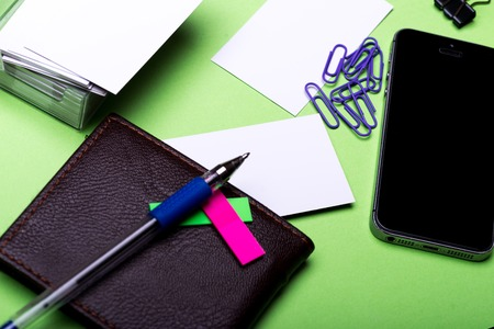 blanks: set of stationery for office: paper clips, binder clip, box with blanks, cell phone, wallet, pen, stickers on green background, side view, selective focus Stock Photo
