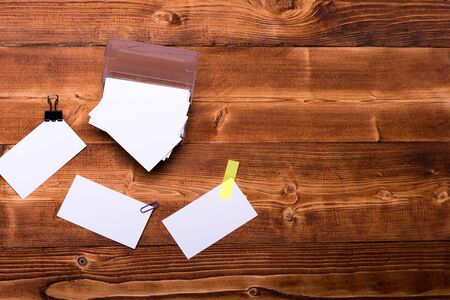 blanks: set of stationery for office: box with blanks, paper clip, binder clip, sticker on brown vintage wooden background, top view, copy space Stock Photo