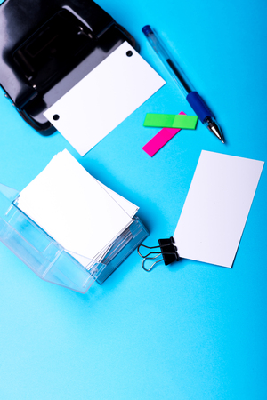 set of stationery for office: hole puncher, box with blanks, binder clip, pen, stickers on blue background, top view, selective focus