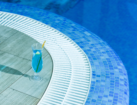 Blue cocktail drink in glass with yellow palm stick on ceramic tile at mosaic swimming pool with water indoors on blurred background Stock Photo