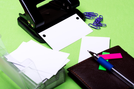 blanks: set of stationery for office: hole puncher, paper clips, box with blanks, wallet, pen, stickers on green background, side view, selective focus
