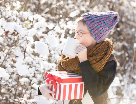 small boy or cute nerd kid in glasses, hat, sweater and fashionable knitted scarf holds red christmas or new year gift box and cup in sunny winter outdoor on natural background