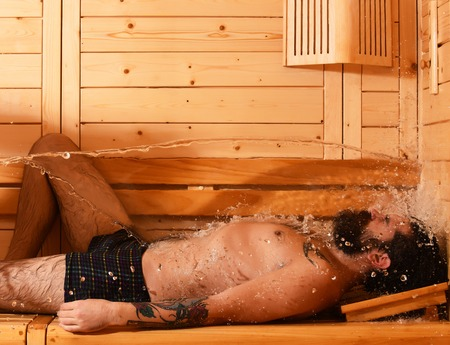 bather: Handsome man or bather, bearded sexy hipster with tattoo on fit body relaxes wet with splash of water in sauna, thermal bath on wooden background Stock Photo
