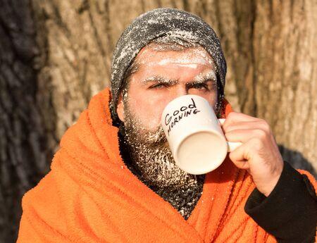 homme congelé, hippie barbu, avec la barbe et la moustache couverte de givre blanc enveloppé dans une couverture orange avec boisson chaude dans la tasse le jour d'hiver en plein air sur fond naturel