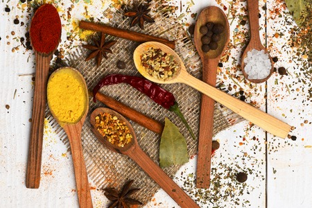 set of various aromatic spices of curry powder or turmeric, paprika, salt, bay leaf, black pepper with spoons, chili pepper and cinnamon on sackcloth on vintage wooden white background, top view Stock Photo