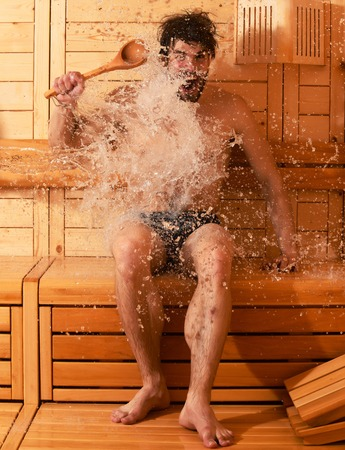 bather: Excited man or bather with muscular sexy torso, body, with spoon wet with big splash of water in sauna, thermal bath on wooden background Stock Photo