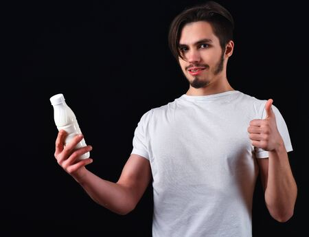 handsome bearded man in white shirt with stylish hair on smiling face holding kefir or yogurt in studio on black studio background Stock Photo - 69880453