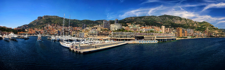 Monte Carlo, Monaco - December 08, 2009: luxury yachts or ships at moorage in sea city port, pier along mountain coast on sunny day on blue sky background