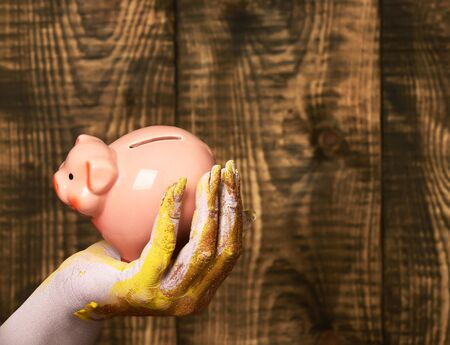 female hand smeared in golden paint or glister holding selective focus pink piggy pig bank on brown vintage studio background, copy space Stock Photo
