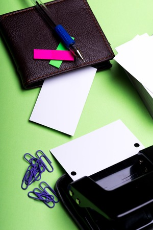 set of stationery for office: hole puncher, paper clips, box with blanks, wallet, pen, stickers on green background, side view Stock Photo