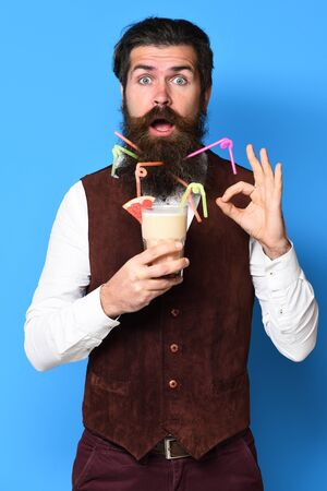 handsome bearded man with long beard and mustache has stylish hair on surprised face holding glass of alcoholic cocktail in vintage suede leather waistcoat on blue studio background