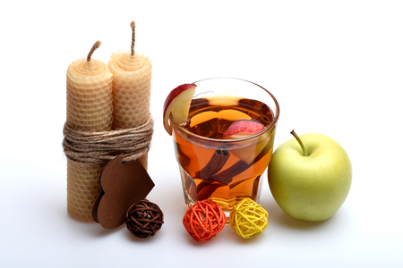 beeswax candle: hot drink of apple tea with cinnamon spice stick or mulled wine in glass, honeycomb wax candle with valentines day heart on rope and decorative straw balls isolated on white background Stock Photo