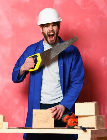 handsome bearded shouting builder man in blue cloak, white helmet and building tools on table holding saw in studio on pink background