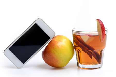 hot drink of apple tea with cinnamon spice stick or mulled wine in glass and mobile or cell phone isolated on white background, copy space Stock Photo