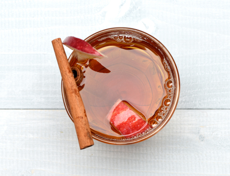 hot drink of apple tea with cinnamon spice stick or mulled wine in glass on wooden background Stock Photo