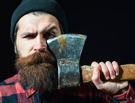 ax man: Handsome man or lumberjack, bearded hipster with beard and moustache in hat holds old rusty iron blade of axe isolated on black background