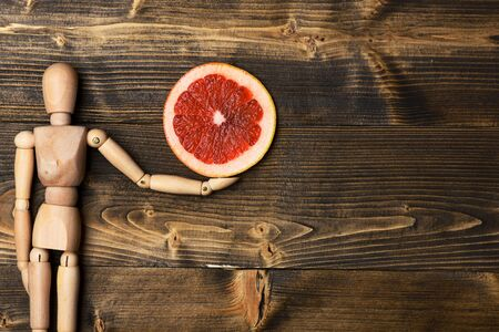 marioneta de madera: wooden puppet holding colorful fresh grapefruit slice on brown vintage background, copy space