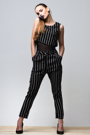 cola mujer: Pretty girl or beautiful woman, fashion model, with sexy blue lips and long hair tail poses in black and white striped suit on grey background