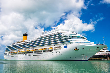 Large luxury cruise ship Disney Wonder on sea water and cloudy sky background docked at port of st.Johns, Antigua
