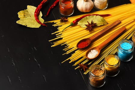badian: italian pasta with spice in jar, chili pepper, badian, bay leaf and garlic on black background as cooking products with wooden spoon, copy space Stock Photo