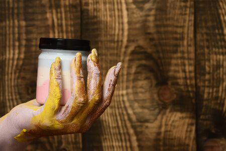 glister: female hand smeared in golden glister holding selective focus jar with colorful paint on brown vintage studio background, copy space