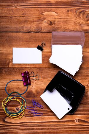 rubber sheet: set of stationery for office: paper clips, binder clips, box with blanks, rubber band, hole puncher on brown vintage wooden background, top view