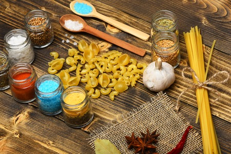 badian: italian pasta with spice in jar, chili pepper, badian and garlic on wood background as cooking products with wooden spoon Stock Photo