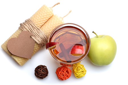 hot drink of apple tea with cinnamon spice stick or mulled wine in glass, honeycomb wax candle with valentines day heart on rope and decorative straw balls isolated on white background Stock Photo