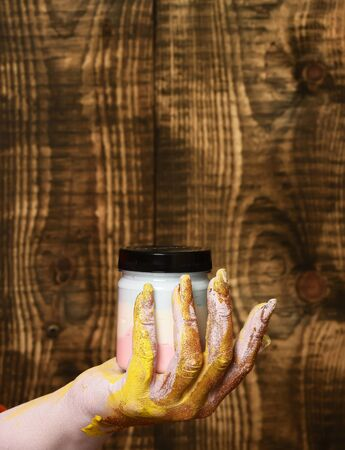 female hand smeared in golden glister holding selective focus jar with colorful paint on brown vintage studio background, copy space
