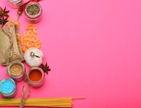 badian: italian pasta with spice in jar, chili pepper, badian, onion and garlic on pink background as cooking products with burlap, copy space