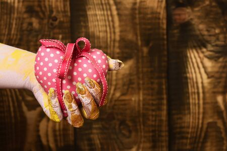 female hand smeared in golden paint or glister holding handmade pink polka dots selective focus valentine heart on brown vintage studio background, copy space