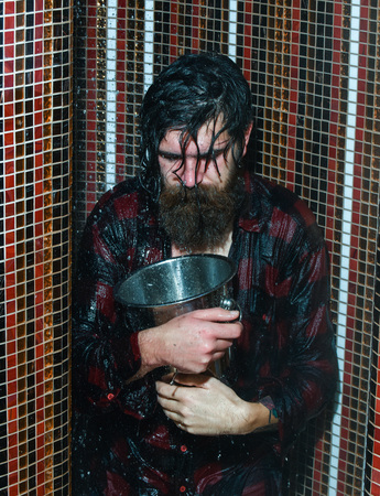 Energized handsome man, bearded hipster with beard and moustache in red checkered shirt pours bucket of water on head in shower on colorful mosaic background