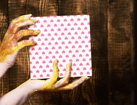 glister: female hands smeared in golden paint or glister holding pink polka dots valentine present box on brown vintage studio background