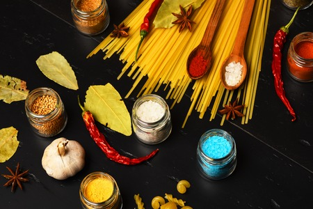badian: italian pasta with spice in jar, chili pepper, badian, bay leaf and garlic on black background as cooking products with wooden spoon Stock Photo