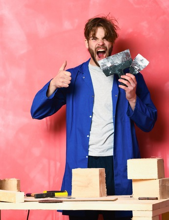 handsome bearded shouting builder man in blue cloak and building tools on table holding putty knifes in studio on pink background Stock Photo