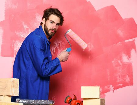 handsome bearded builder man with disheveled hair in blue cloak and building tools on table painting wall with paint roller in studio on pink background