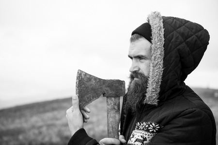 hilt: Handsome man hipster with beard and moustache on serious face in hat and jacket holds rusty axe with wood hilt on mountain top against cloudy sky on natural background, copy space, black and white Stock Photo