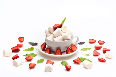 set of cup with marshmallow on plate with sheets of basil and pieces of strawberry laid out in circle isolated on white background, side view