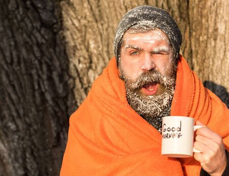 Winking frozen man, bearded hipster, with beard and moustache covered with white frost wrapped in orange blanket with warming drink in cup on winter day outdoors on natural background