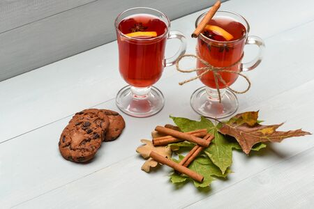 badian: chocolate cookies with hot drink of mulled wine or tea with cinnamon spice stick in glass near green autumn leaves at christmas on grey wooden background