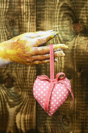 female hand smeared in golden paint or glister holding handmade pink polka dots valentine heart on brown vintage studio background, selective focus Stock Photo