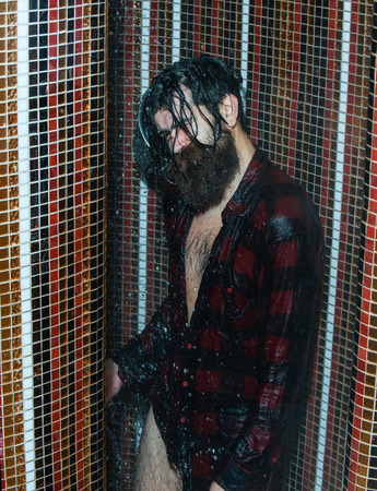 Energized handsome man, bearded hipster with beard and moustache in red checkered shirt pours ice water on head in shower on colorful mosaic background