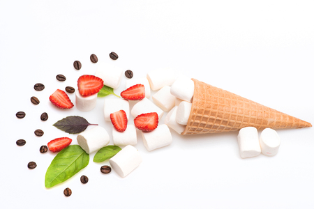 set of ice cream cone with marshmallow, roasted coffee beans, pieces of strawberry and sheets of basil isolated on white background, top view