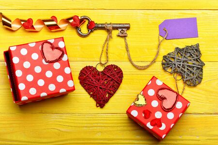 Set of colorful present boxes near metallic key with purple label or tag, festive ribbon and big handmade valentine hearts on vintage yellow wooden background, top view