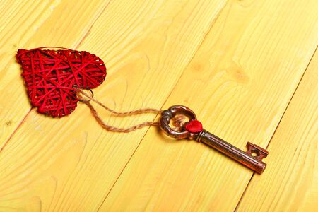 Old metallic key with big handmade red valentine heart on yellow vintage wooden background, top view