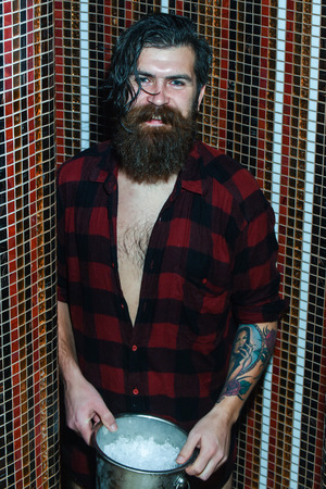 Cheerful handsome man, bearded hipster with beard and moustache in red checkered shirt wet with water in shower with metal ice bucket on colorful mosaic background Stock Photo