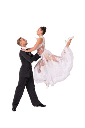 beautiful ballroom dance couple in a dance pose isolated on white background. sensual proffessional dancers dancing walz, tango, slowfox and quickstep, girl doing high jump Stock Photo