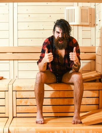 bather: Excited man or bather, bearded hipster with beard and moustache in red checkered shirt wet of water shows thumbs up gesture in sauna, thermal bath on wooden background Stock Photo