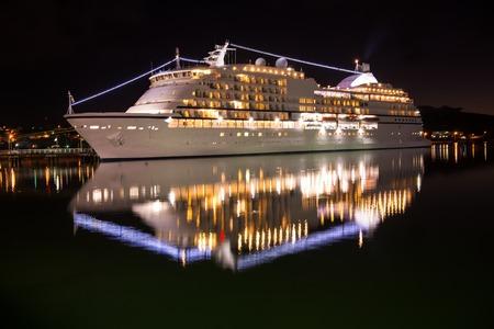 Large luxury cruise ship on sea water at night with illuminated light docked at port of st.Johns, Antigua
